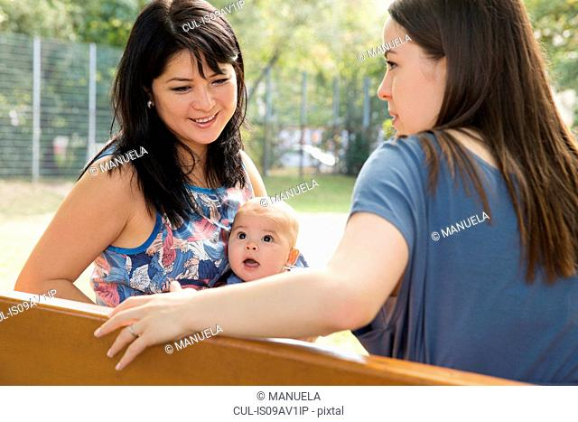 Grandmother sitting on park bench with daughter and baby granddaughter