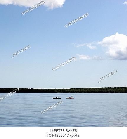 Two people in canoes on a lake