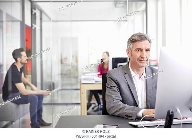 Mature businessman and coworkers working in office