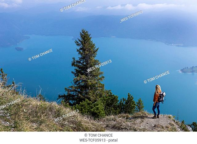 Young woman hiking in the Bavarian mountains, looking at Lake Walchensee