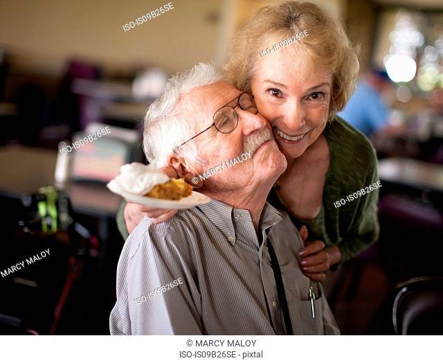 Senior woman hugging senior man, smiling