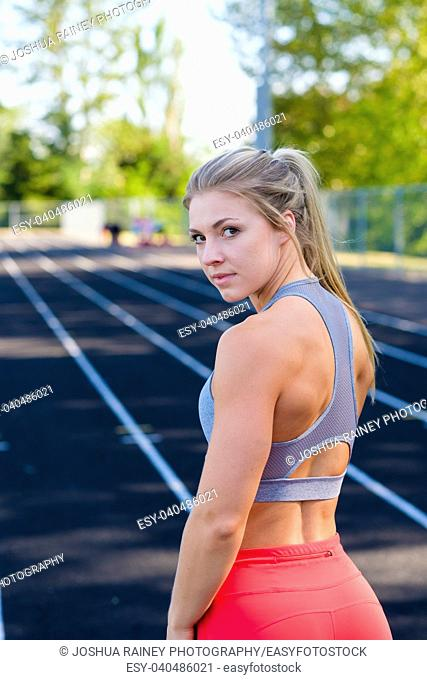Very pretty girl looks back towards the camera while working out on an outdoor track in the summer