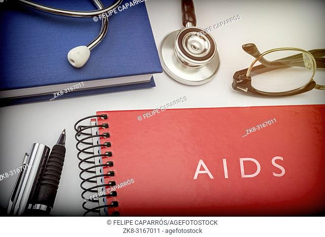 Titled red book aids along with medical equipment, conceptual image