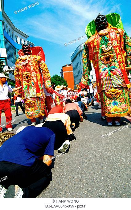 People praying in front of goddess statues during mazu festival, China