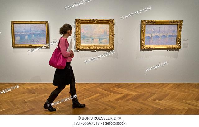 A woman walks through the big Claude Monet exhibition and past the paintings 'Waterloo Bridge, Sonne' (l-r), 'Waterloo Bridge