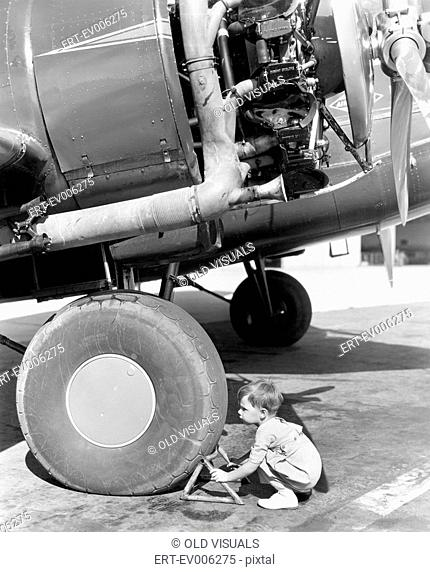 Little boy trying to fix an airplane wheel All persons depicted are not longer living and no estate exists Supplier warranties that there will be no model...