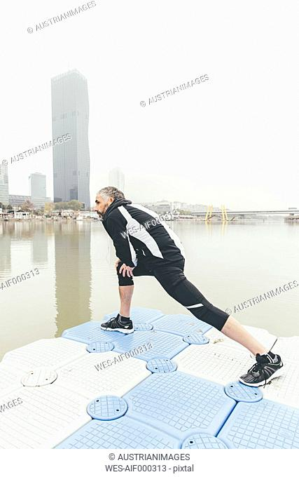 Austria, Vienna, jogger doing stretching exercise on Danube Island