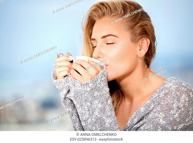 Portrait of beautiful happy sensual girl with closed eyes enjoying tasty strong morning coffee, having breakfast in outdoors cafe