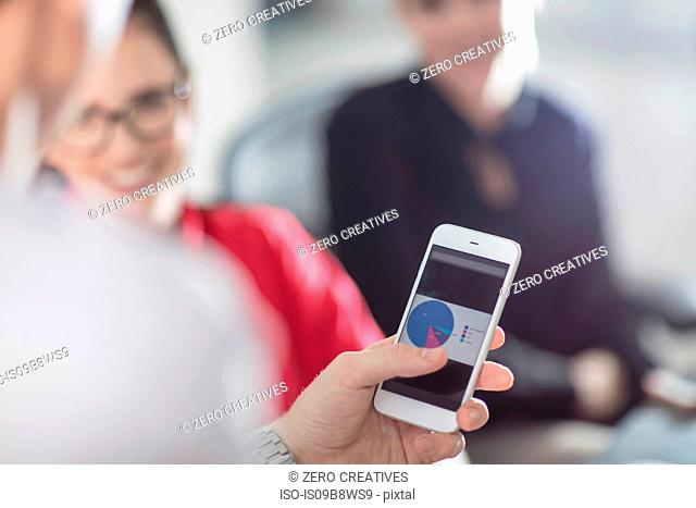Hand of male office worker holding smartphone