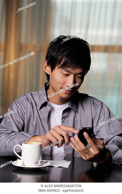 Young man sitting at a table texting on phone