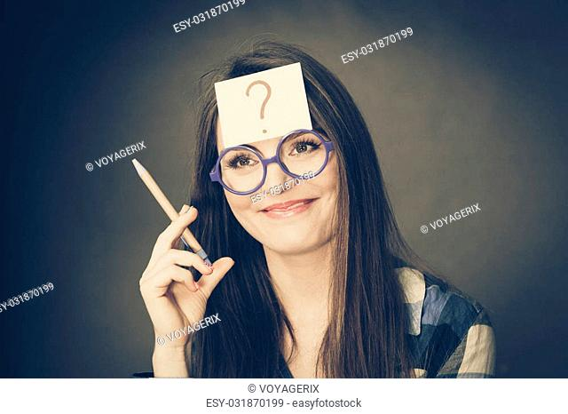Woman confused thinking seeks a solution, paper card with question mark on her head. Doubtful young female in glasses studio shot on black