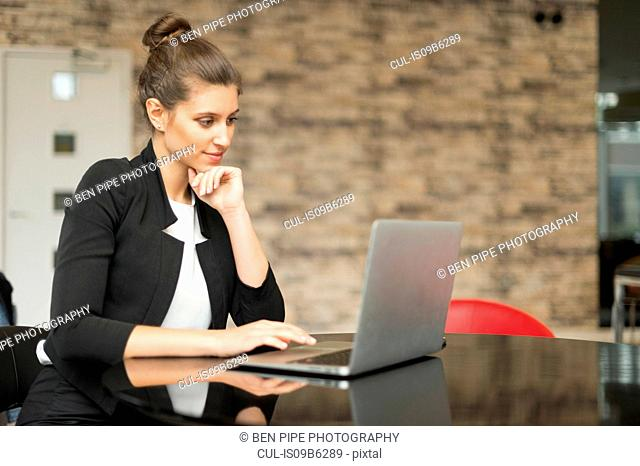 Young businesswoman looking at laptop on office desk