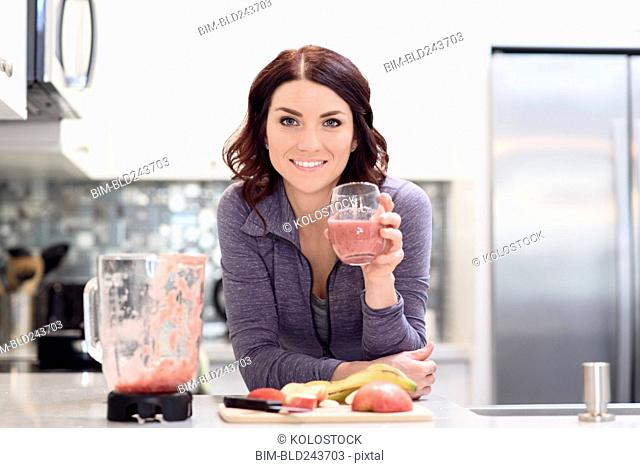 Caucasian woman drinking fruit smoothie in domestic kitchen