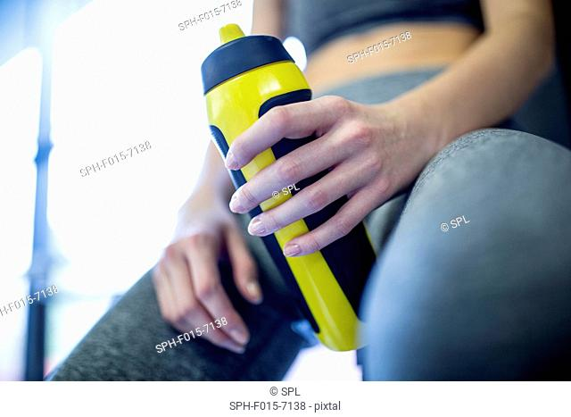 MODEL RELEASED. Woman holding water bottle in gym, close-up