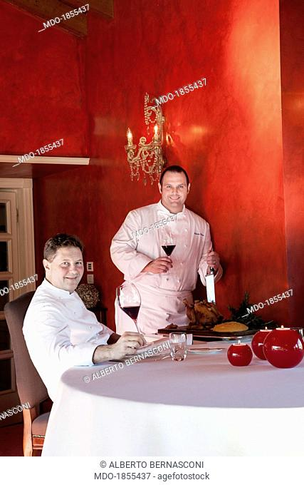 Italian chefs Enrico Cerea known as Chicco (sitting at the table) and Roberto Cerea (standing) holding a goblet of wine in a photocall shooted at his restaurant...