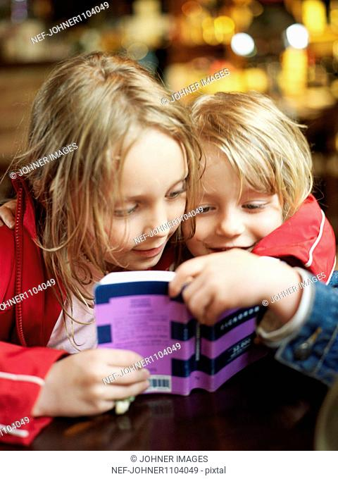 Two kids reading book