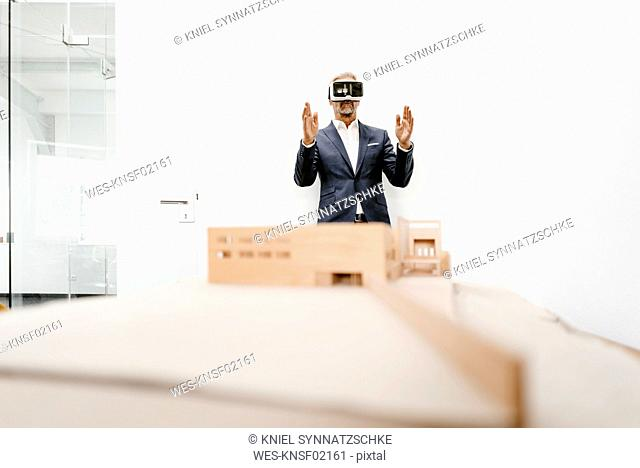Mature businessman with architectural model in office wearing VR glasses