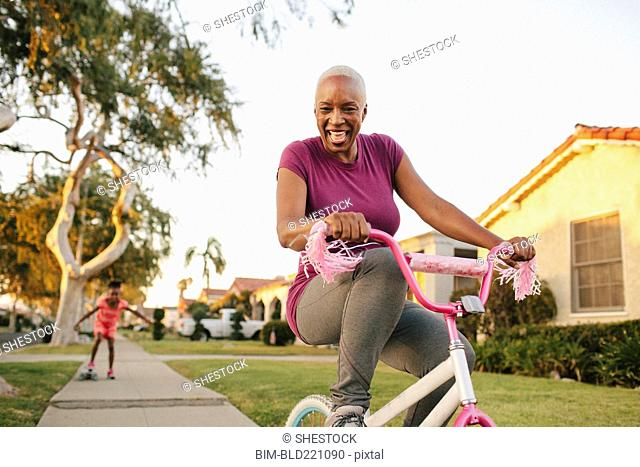Mother and daughter riding skateboard and bicycle