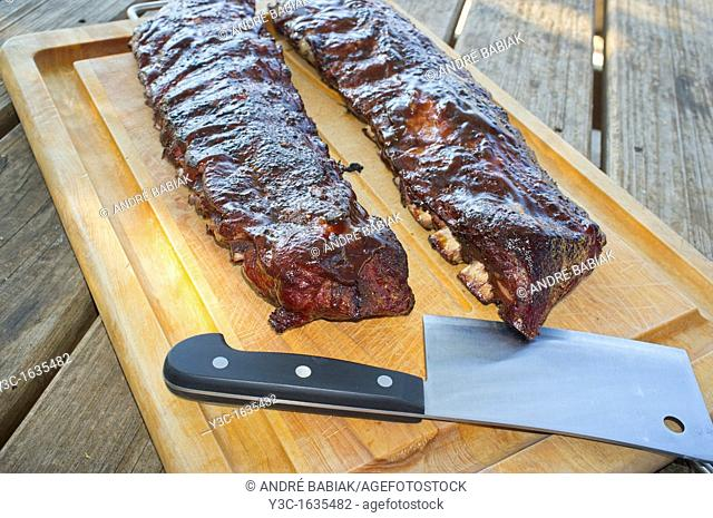 Spare ribs and meat cleaver on a cutting board