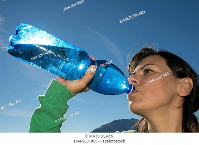 Woman Drink Water From a Blue Bottle With Sunlight in Switzerland