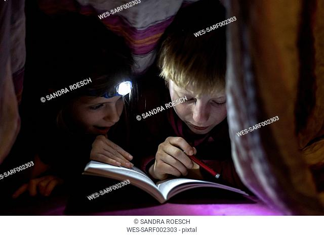 Brother and sister reading book under a blanket