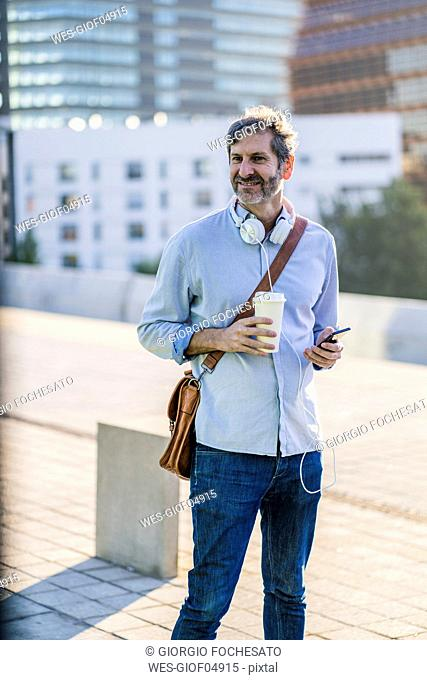 Portrait of smiling mature man with takeaway coffee, headphones and cell phone in the city