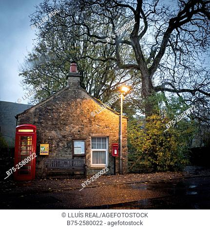 Little cottage in a typical Yorkshire Dales Village in the evening, with phone box, post box, a bench and a street lamp post