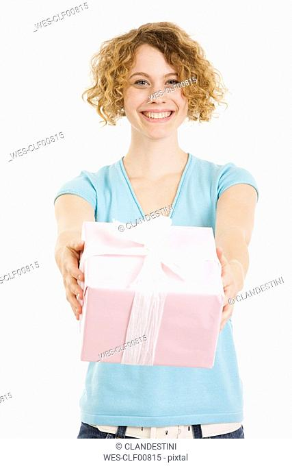 Young woman holding gift parcel, smiling, portrait