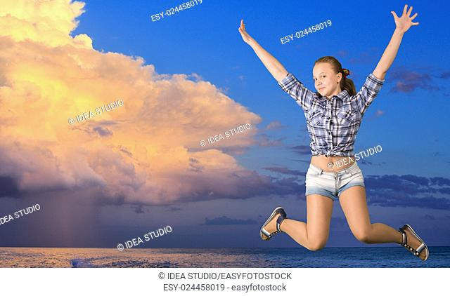 Teen girl jumping over the sea with clouds