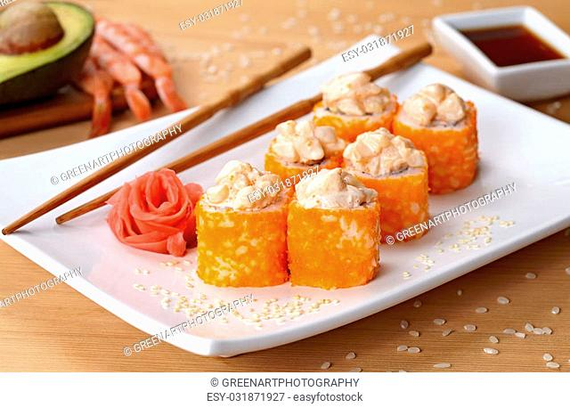 California deluxe sushi roll with tobiko caviar and spice. Traditional asian rice sushi healthy seafood. White plate, wooden table background
