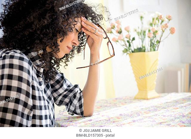 Anxious mixed race woman sitting at table