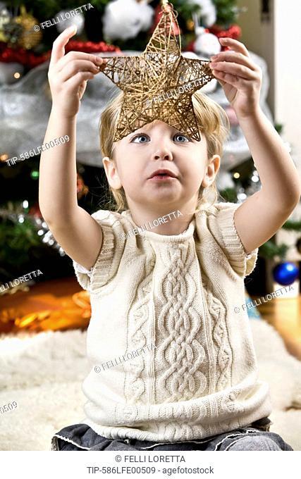 girl holding a Christmas star