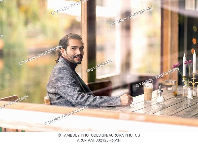 A Hispanic startup business entrepreneur or freelancer sitting at a cafe and smiling at camera