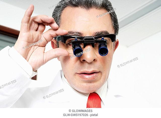 Close-up of a male doctor adjusting lupa binoculars