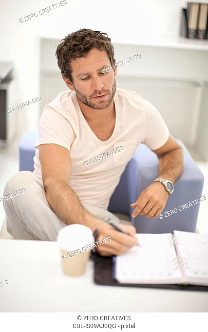 Mid adult man making notes