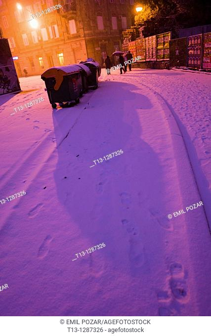 Snow covered street, long shadow from a trash cart. Rijeka, Croatia