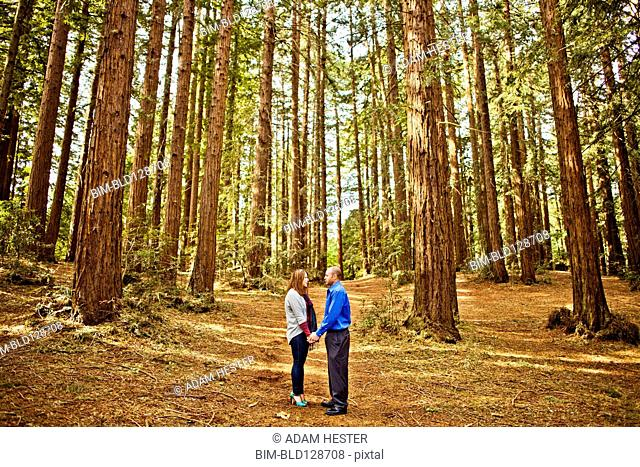 Hispanic couple holding hands in forest