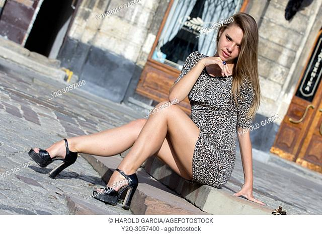Sexy Ukrainian woman wearing a leopard skin print dress posing seated on the floor for a photographic sequence in the ancient city of Lviv, Ukraine