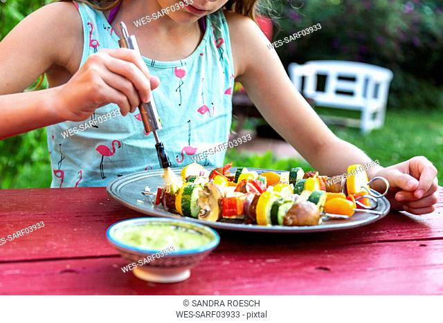 young girl spreading vegetarian grill skewers with Argentinian chimichurri