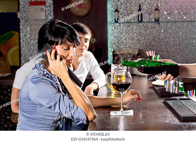 Woman chatting on her mobile while drinking at the bar in a nightclub listening to the conversation while the barman pours her another drink