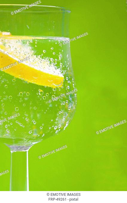 Zitrone in einem Wasserglas mit grünem Hintergrund