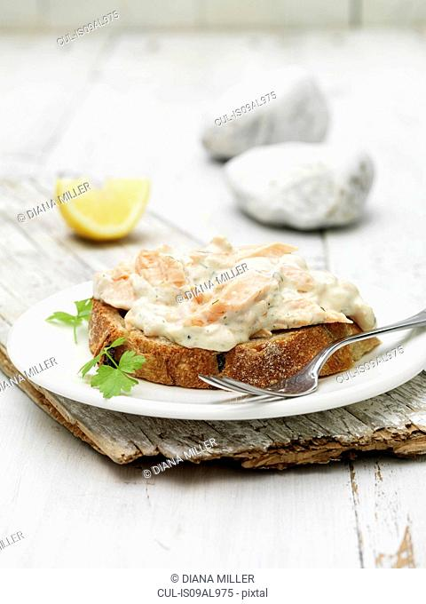 Poached & smoked salmon cocktail and dill sauce on bread with coriander garnish