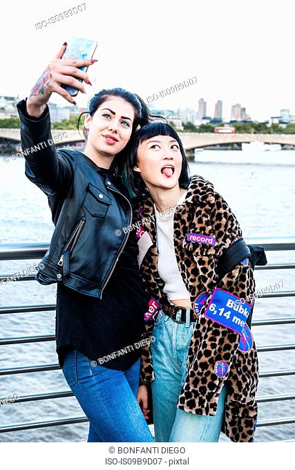 Two young stylish women taking smartphone selfie on millennium footbridge, London, UK