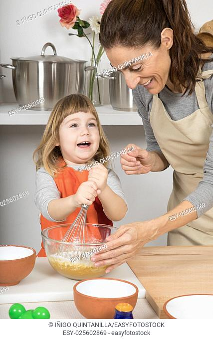 three years old happy child, and woman mother in teamwork, whipping cream in glass bowl with metal whisk to make and cook a sponge cake at kitchen home