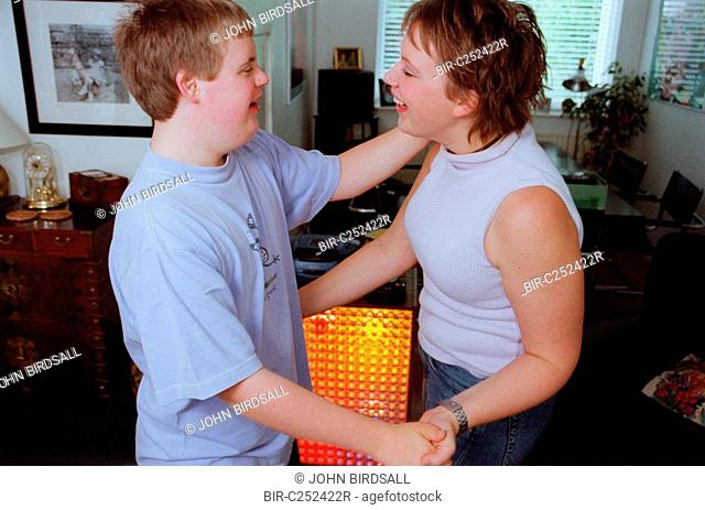 Teenage boy with Downs Syndrome dancing with sister in living room