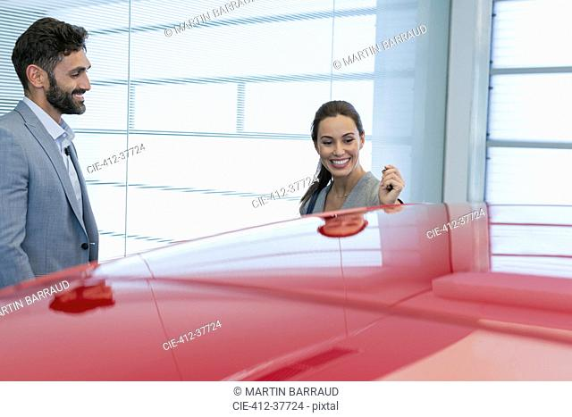 Smiling car salesman showing new red car to female customer in car dealership showroom