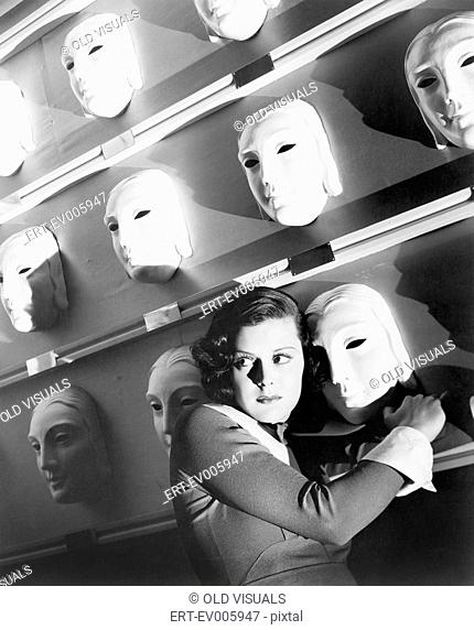 Woman looking frightened holding onto one mask on the wall of masks All persons depicted are not longer living and no estate exists Supplier warranties that...