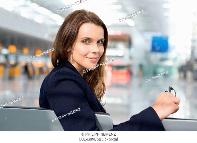 Portrait of businesswoman looking over her shoulder in airport departure lounge