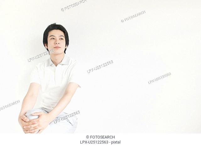 Young man sitting and looking away