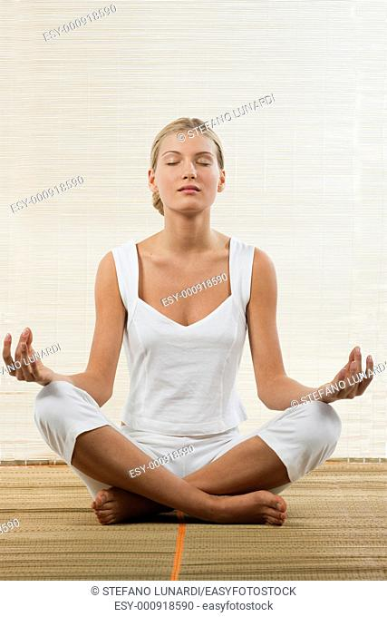 Young woman sitting in lotus position and meditating
